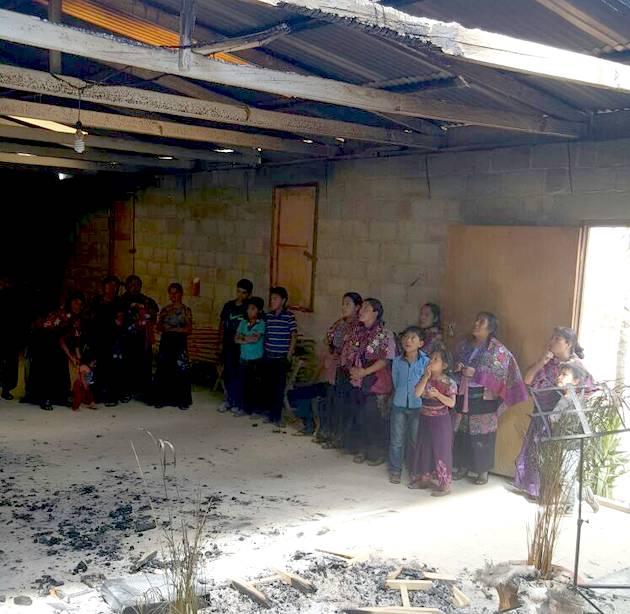 Miembros de la iglesia contemplan el templo incendiado