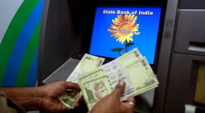 FILE PHOTO - A man counts money after withdrawing it from a State Bank of India automated teller machine (ATM) in Mumbai, India, March 9, 2016. REUTERS/Danish Siddiqui/File Photo