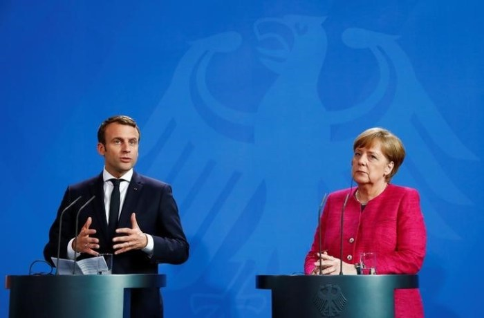 German Chancellor Angela Merkel and French President Emmanuel Macron address a news conference at the Chancellery in Berlin