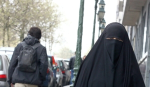A muslim woman dressed in niqab walks through the streets of Brussels