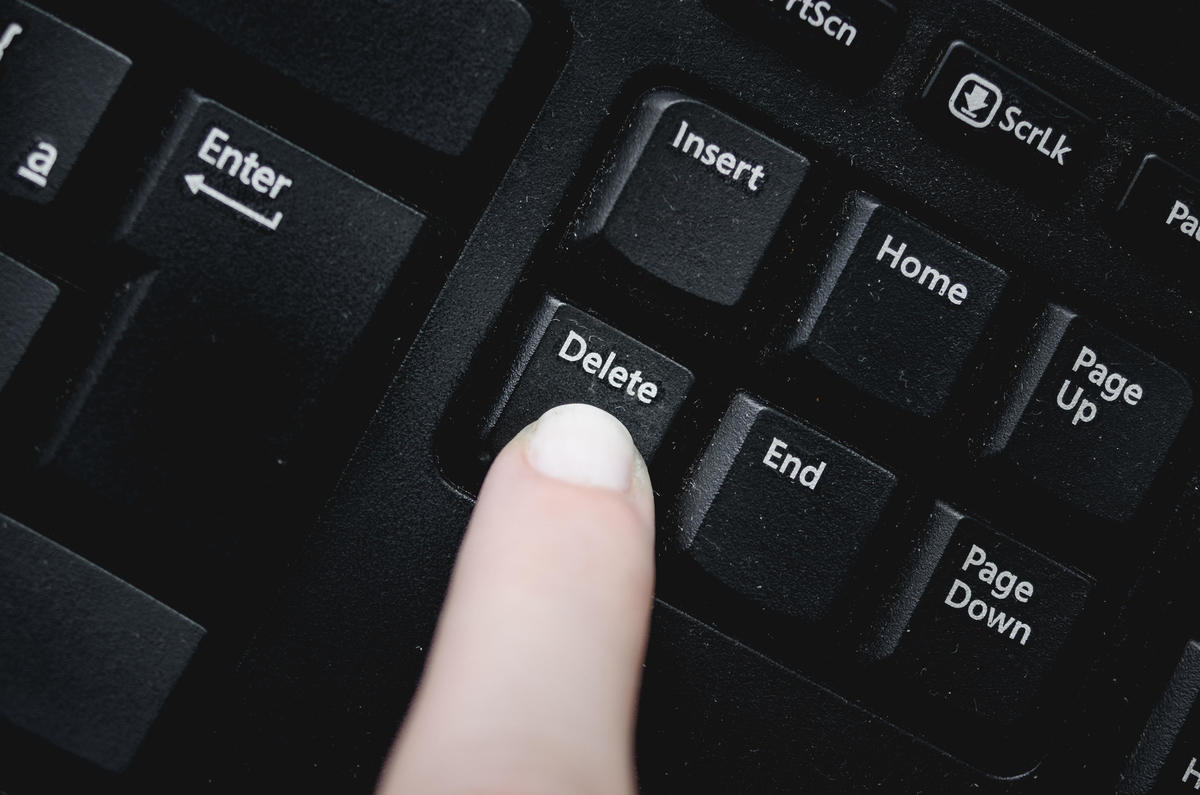 Finger over the delete key from a dusty black keyboard